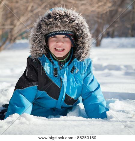 Boy In Winterwear Laughing While Playing In Snowdrift Outside