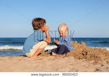 Brother And Sister Playing In Sand At Beach