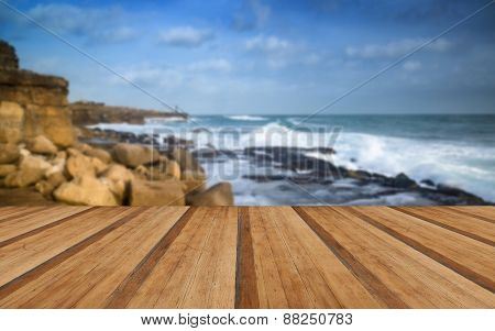 Landscape Of Waves Crashing Onto Rocks During Beautiful Winter's Day With Wooden Planks Floor
