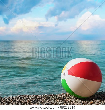 Children's Inflatable Ball On The Beach Against The Sea