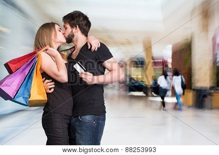 Happy Kissing Couple With Shopping Bags At The Mall
