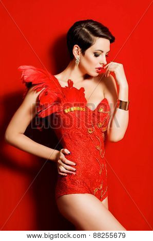 Young beautiful girl in a dancing suit with feathers