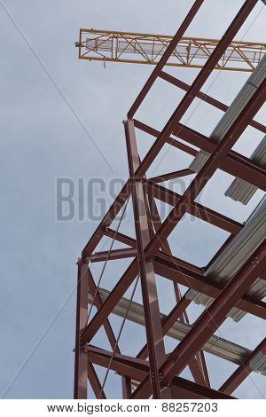 A top view of a yellow tower crane and red steel structure on a construction site