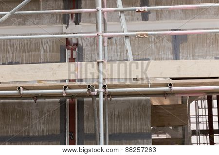 A detailed view of concrete and red steel intersect with temporary steel support