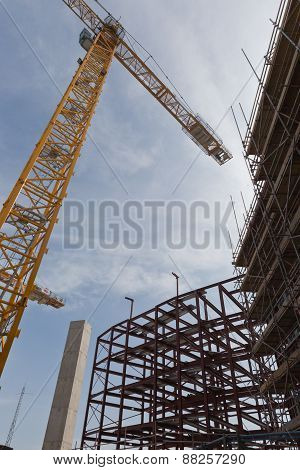 A view of a yellow tower crane and red steel and concrete structure on a building site