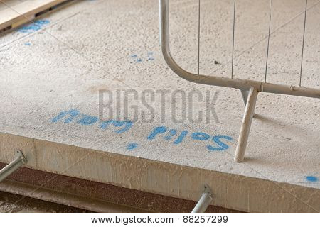 A written note saying solid wall sprayed on a concrete slab on a a construction site
