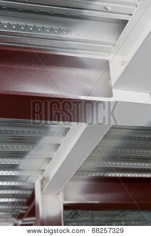 A view of a red steel column intersecting a beam on the underside of a standard metal profiled deck
