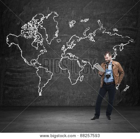 Handsome Tourist Is Examining The Map. Black Wall With The Sketch Of The World Map.