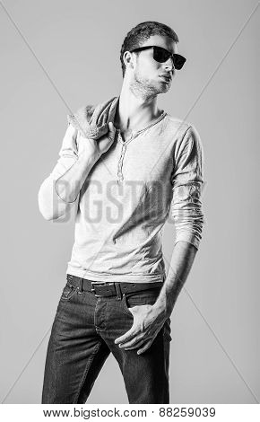 Fashion Shot: Handsome Young Man Wearing Jeans, Shirt And Sunglasses. Black And White