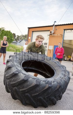 Strong man flips heavy tire outdoor as workout