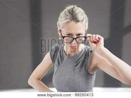 Strict teacher looking through glasses with serious expression