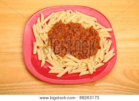 Penne Bolognese On Red Plate