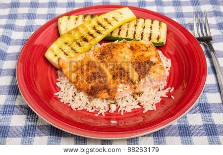 Salmon On Rice With Squash On Red Plate