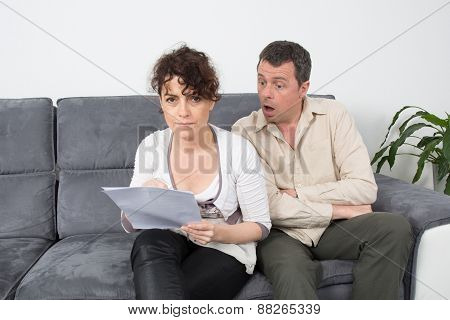 Happy Couple Reading A Paper In Their Living Room