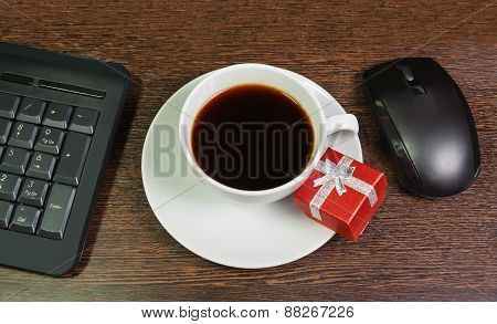 Composition With  The Cup Of Coffee, Red Gift Box, Mouse And Keyboard Laying On Wooden Desk