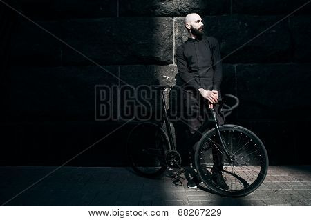 bearded guy in black clothes with fix bike