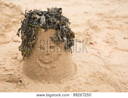 Sandcastle with seaweed making a smiling face