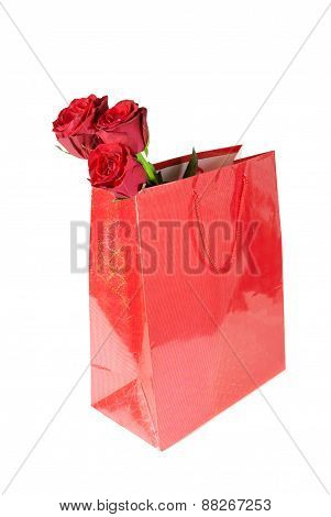 Three Red Roses In A Red Gift Bag On White Background