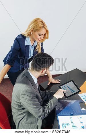 Businessman And Businesswoman Looking At Business Document In Digital Tablet