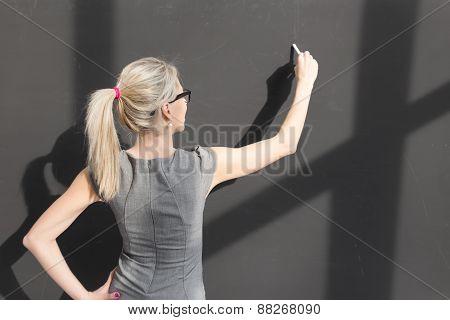 Teacher writing with white chalk on empty blackboard in classroom