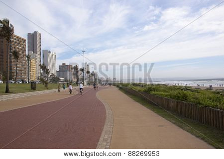 Many Unknown Pedestrians And Cyclist On Paved Promenede