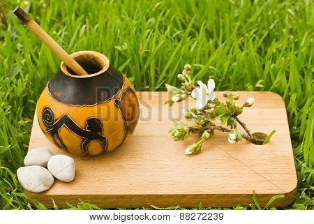 herbal tea mate in kalabas on wooden board with grass background