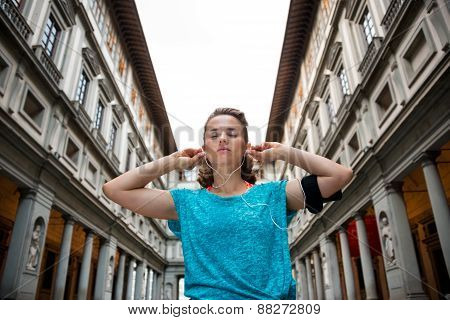 Fitness Woman Wearing Earphones Near Uffizi Gallery In Florence,