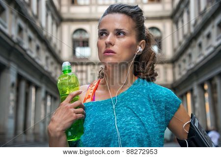 Thoughtful Fitness Woman With Bottle Of Water Near Uffizi Galler