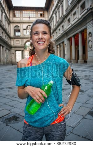 Happy Fitness Woman With Bottle Of Water Near Uffizi Gallery In Florence, Italy