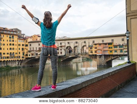 Fitness Woman Rejoicing In Front Of Ponte Vecchio In Florence, Italy. Rear View