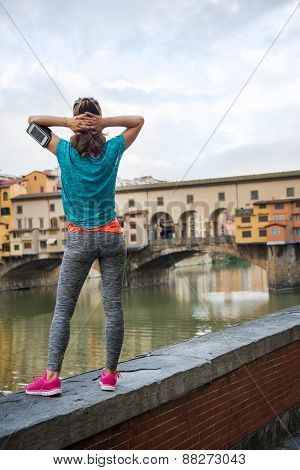 Fitness Woman Standing In Front Of Ponte Vecchio In Florence, Italy. Rear View