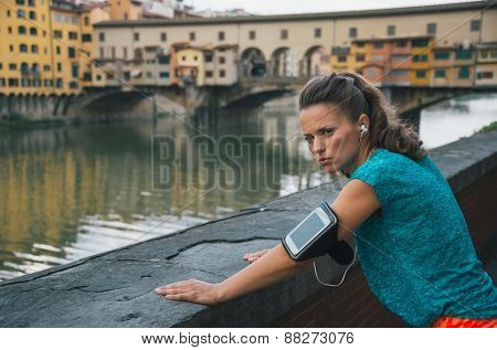 Serious Fitness Woman Standing In Front Of Ponte Vecchio In Florence, Italy