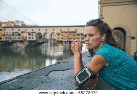 Thoughtful Fitness Woman Standing In Front Of Ponte Vecchio In Florence, Italy