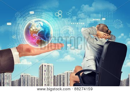Business woman sitting in chair and hand holding globe