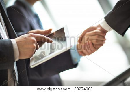 Hands of people working with tablet computer.