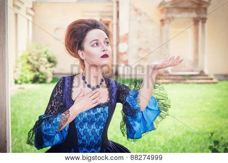 Beautiful Woman In Blue Medieval Dress Stretching Hand To Something