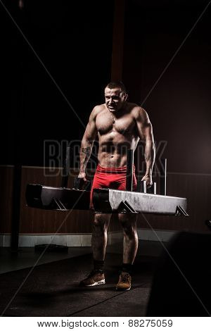 Very power athletic guy execute exercise in sport hall.