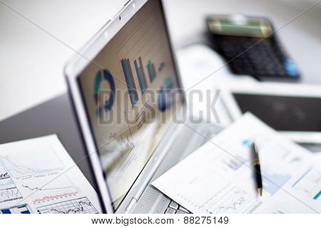 Businessman analyzing investment charts with laptop.
