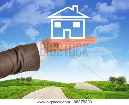 Businessmans hand holding wire-frame house