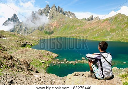 Man admiring a beautiful lake in the mountains