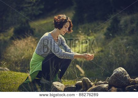 Woman Washing Hands In Mountain Stream Water