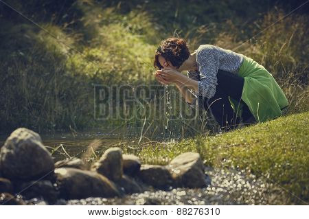 Woman Drinking Creek Fresh Water