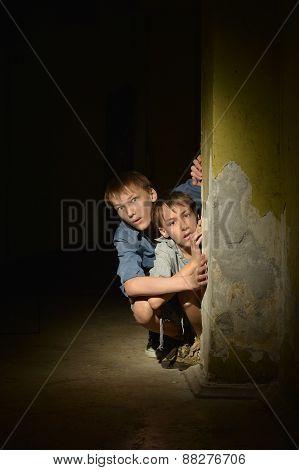 Two  boys sitting in a dark cellar