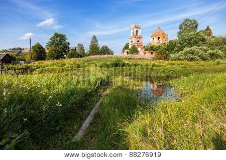 Traditional Russian Landscape With Small Tranquil River And Old Abandoned Church In The Background