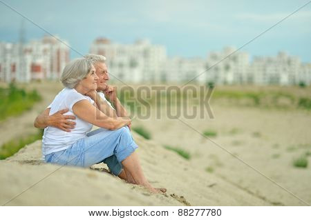 Elderly couple sitting on sand