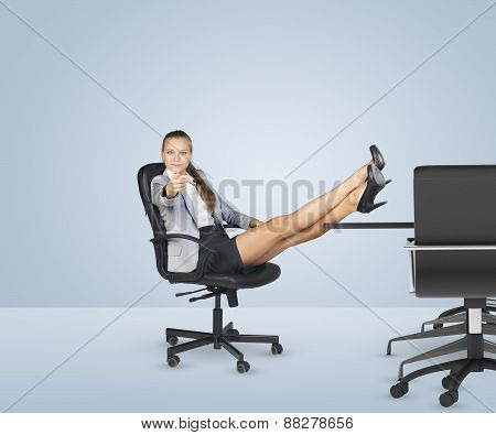 Businesslady sitting in chair with her crossed legs on table