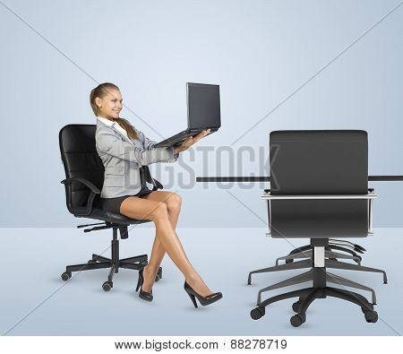 Businesslady sitting half-turned in chair and looking at laptop
