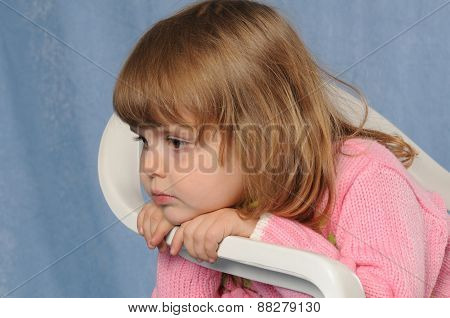 Little Sad Girl On White Chair At Studio Portrait