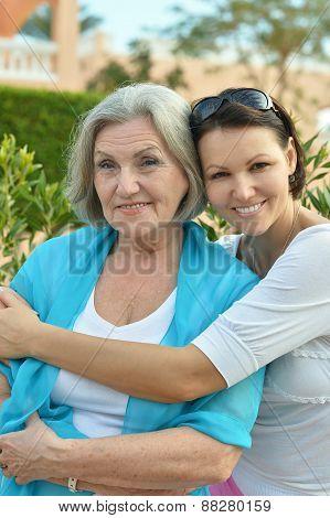 daughter hugging elderly mother