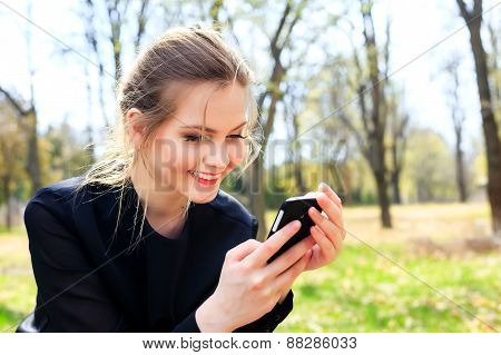 Happy Girl With Disheveled Hair Looking Into Smartphone Smiling